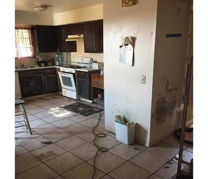 Photo of messy kitchen, white wall with mold on right side.