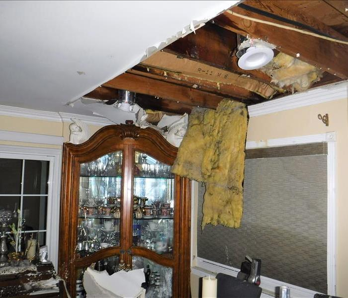 Open ceiling caused by water damage in dinning room area above a china cabinet