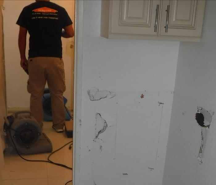 Technician facing his back checking moisture reader, equipment placed on floor, hole on wall located in right corner.