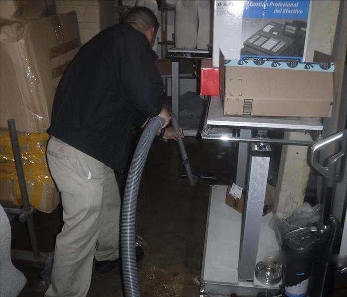 Technician extracting water from a floor with his equipment.