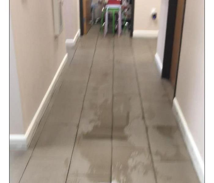 Photo of hallway at an office with water on marble floor.
